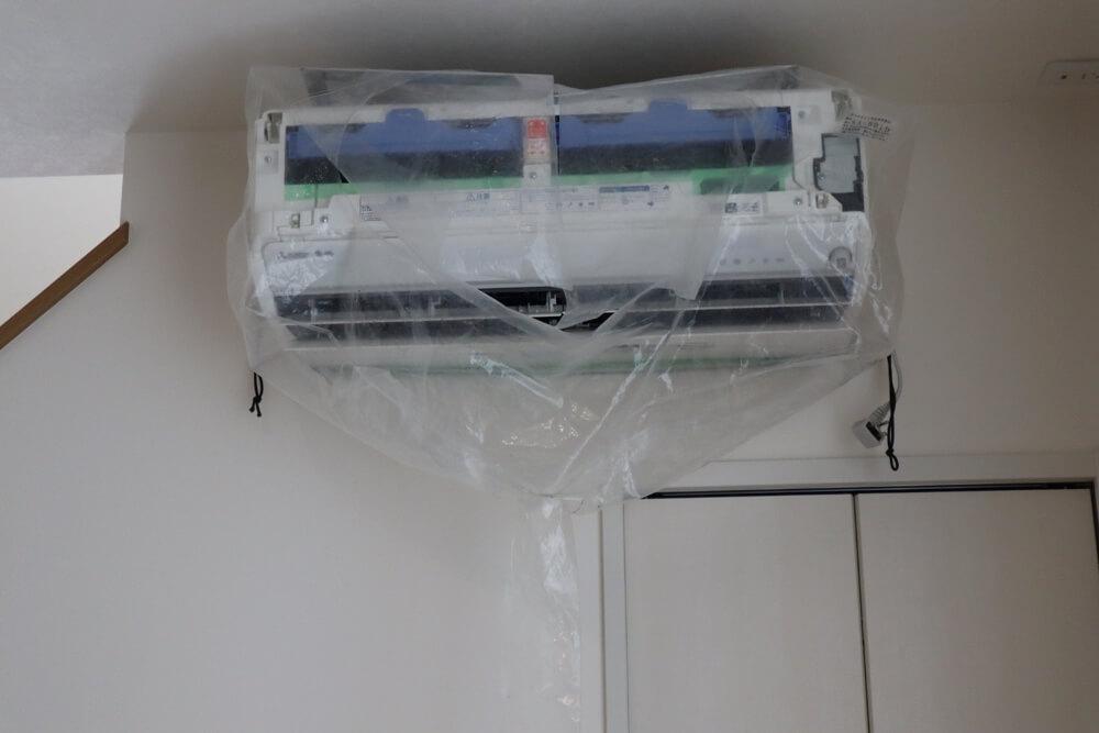 エアコンクリーニングの内部洗浄を前にきれいに養生されたエアコン